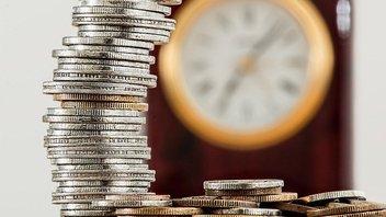 Stapel von Münzen, im Hintergrund eine Uhr