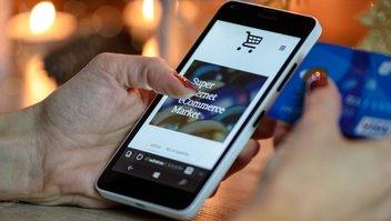 Eine Frau bezahlt in einem Online-Shop mit einer Kreditkarte.
