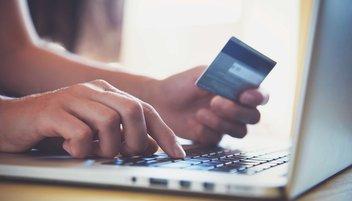 Une personne saisit les données de sa carte bancaire sur internet pour un paiement en ligne.